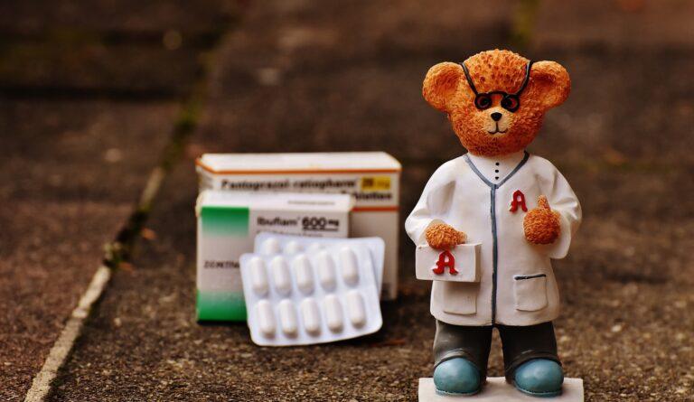 Apotheker-Bärenfigur mit Medikamenten im Hintergrund